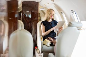 25762159 - rich mid adult woman using tablet computer in private jet