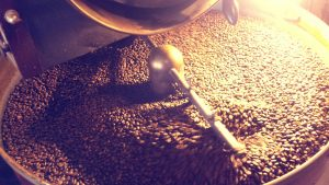 35514396 - coffee beans being stirred around in a roasting machine.