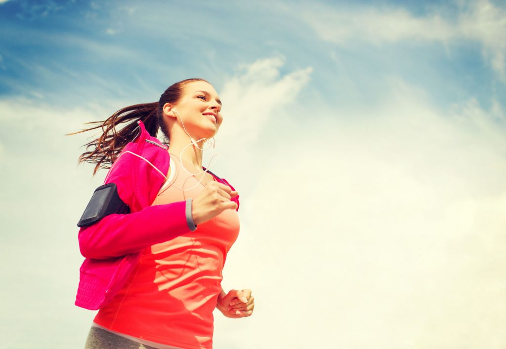 35172316 - fitness, sport and lifestyle concept - smiling young woman with earphones running outdoors