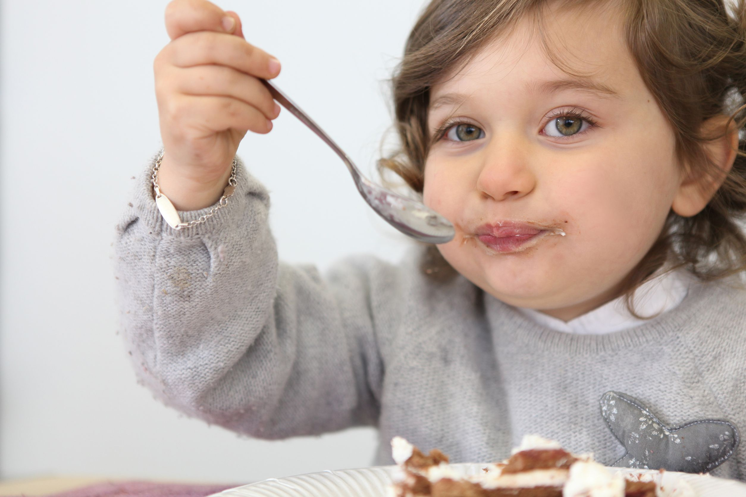 11135641 - young girl eating a piece of cake